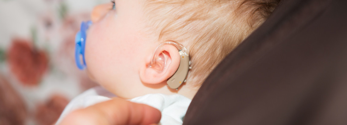 Cute baby boy with hearing aid